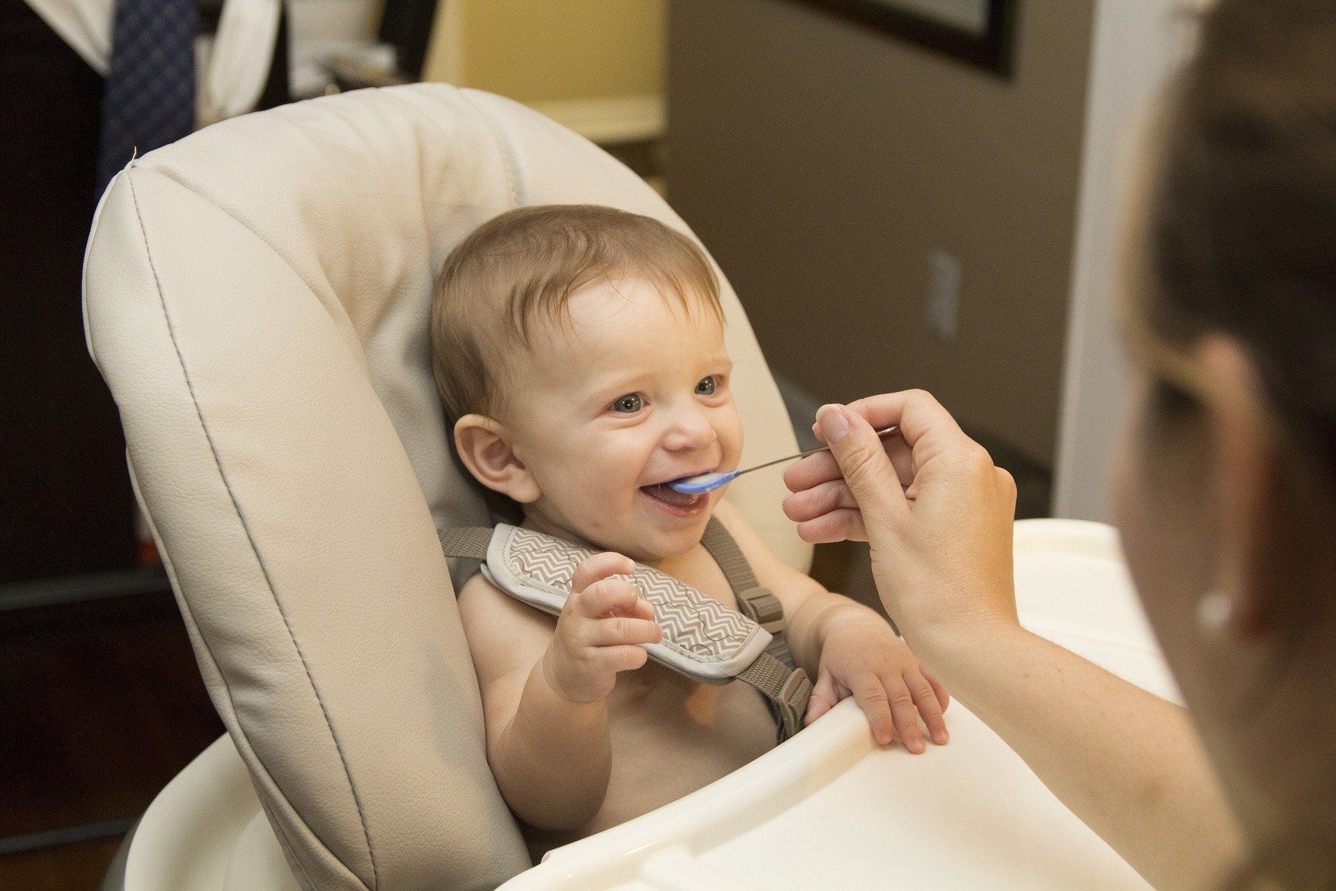 Baby being fed in highchair.