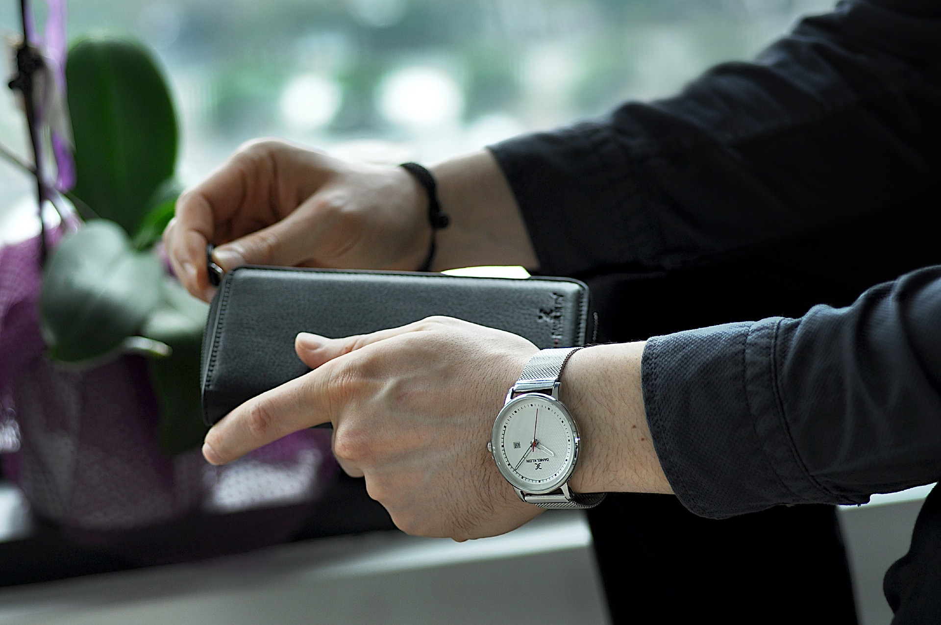 mans hands wearing a watch and holding a wallet