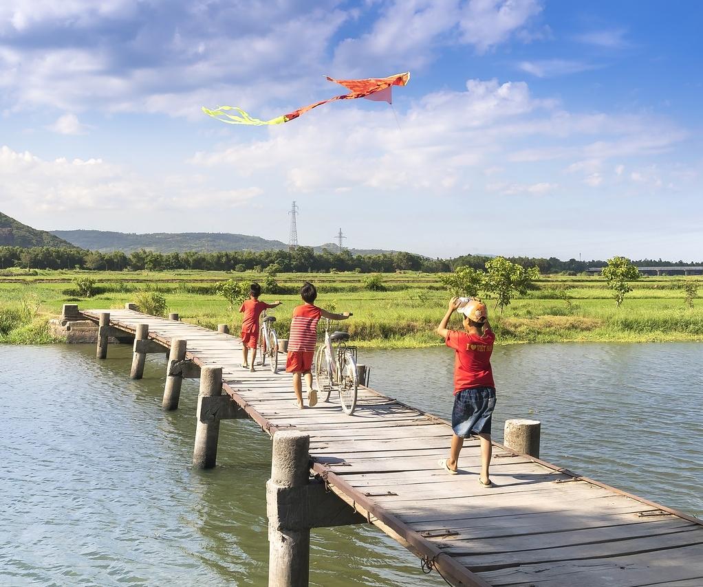 3 children walking across a bridge over an Asian river whilst holding their bikes.
