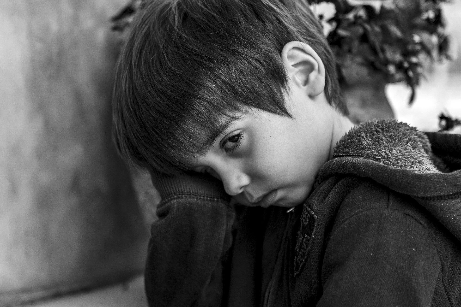 Boy sad against a wall