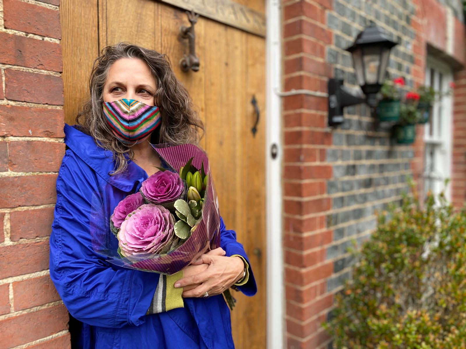 Lady wearing face mask, holding flowers